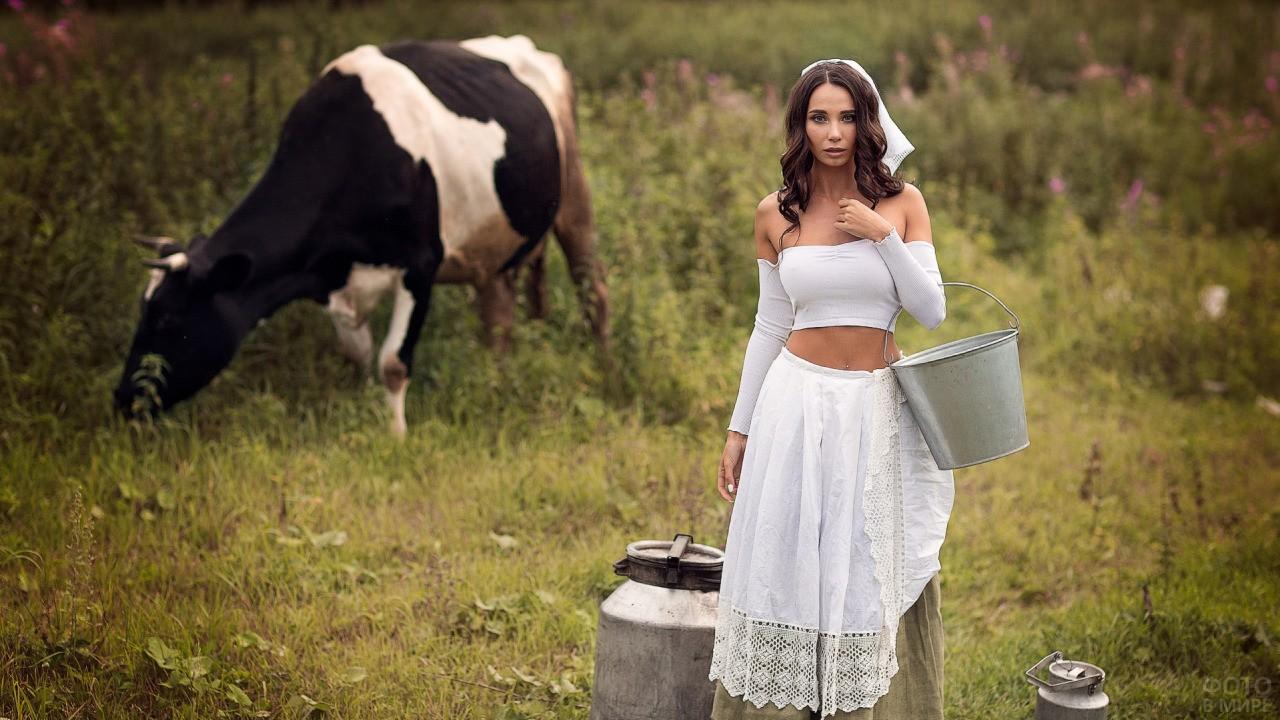Доярка стоит с ведром рядом с коровой