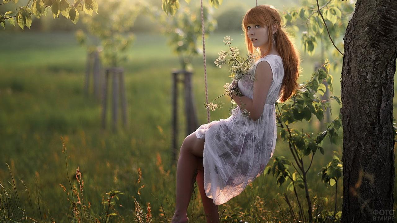 Рыжеволосая девушка сидит на качелях с цветами в руках