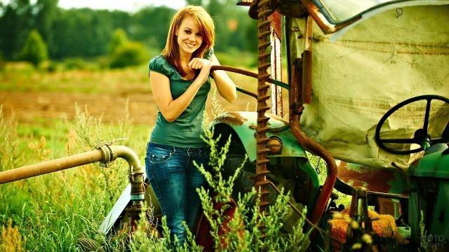 Сельская девушка стоит около трактора