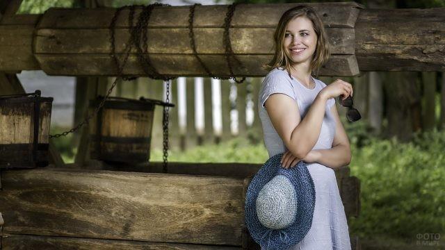 Улыбающаяся девушка держит шляпу у колодца