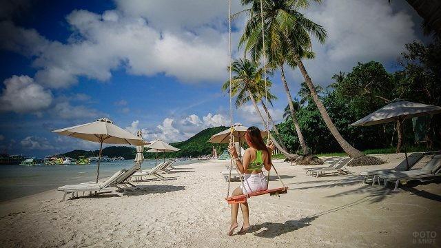 Девушка качается на качелях на пляже Фукуок