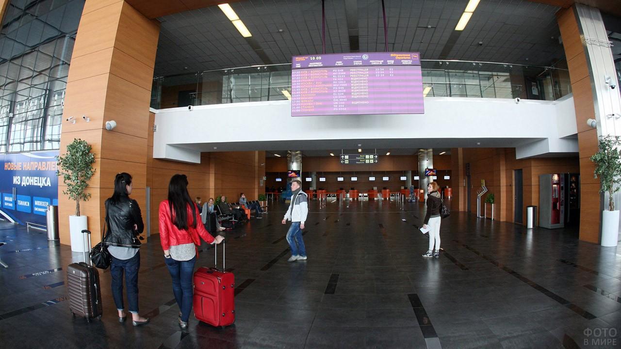 Пассажиры у табло в зале ожидания