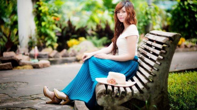 Азиатка в синей юбке на лавочке в парке