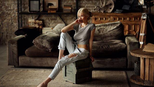 Блондинка сидит на ящике в лофте