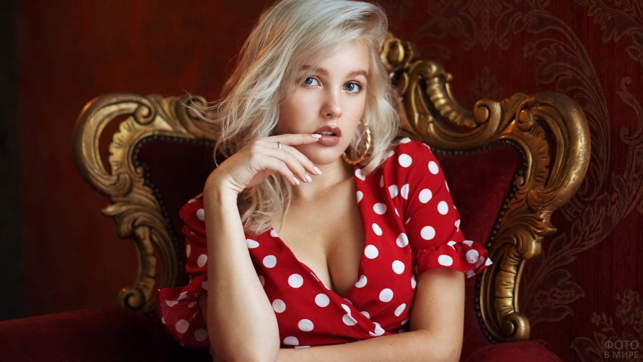 Блондинка в платье в горох в резном кресле