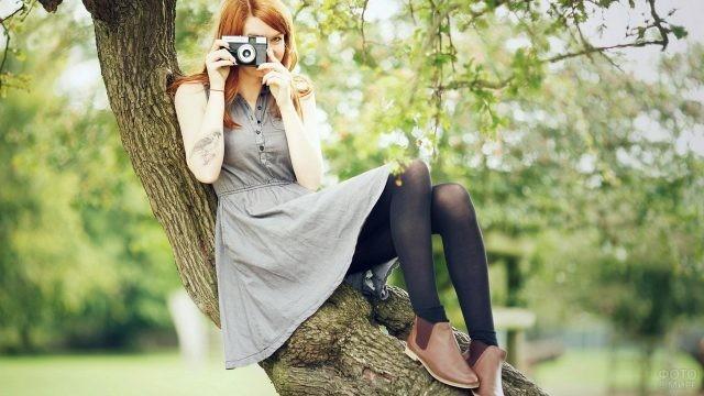 Девушка фотографирует на дереве