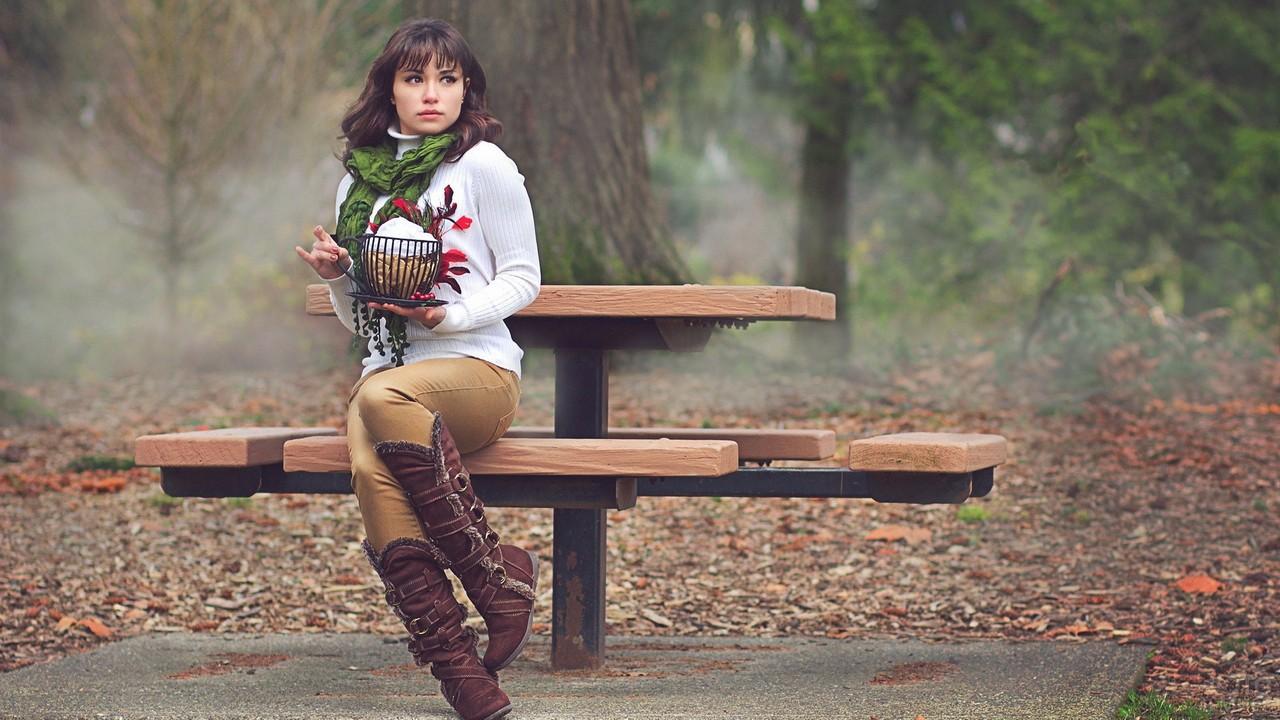 Девушка на скамейке в туманном лесу