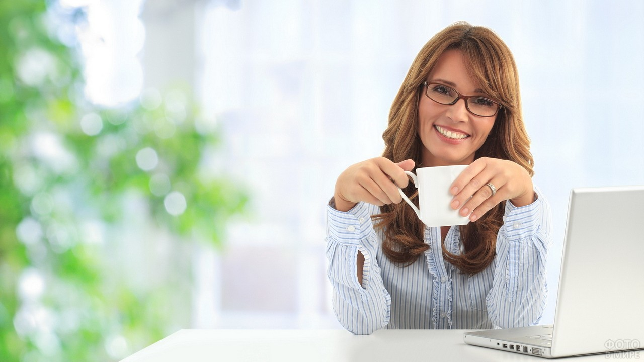 Девушка с бокалом сидит за ноутбуком