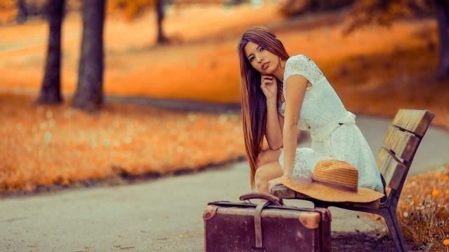Девушка с чемоданом на лавочке в парке