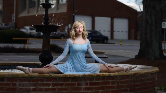 Девушка сидит на шпагате у фонтана