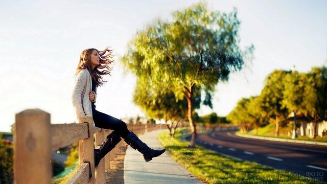 Девушка сидит на заборе