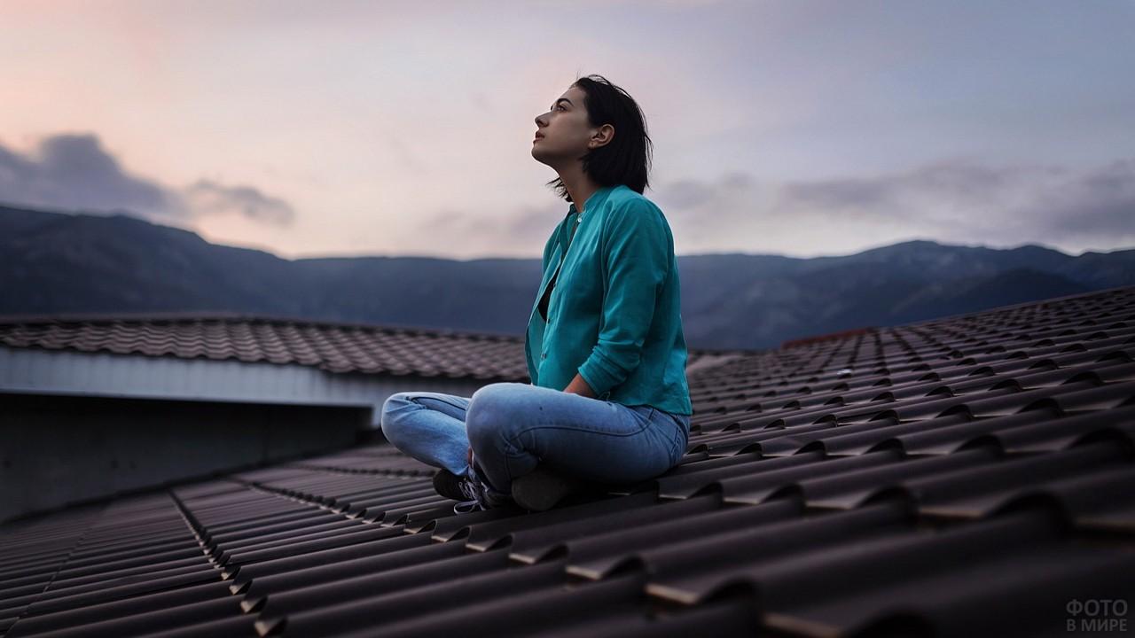 Девушка смотрит в небо, сидя на крыше