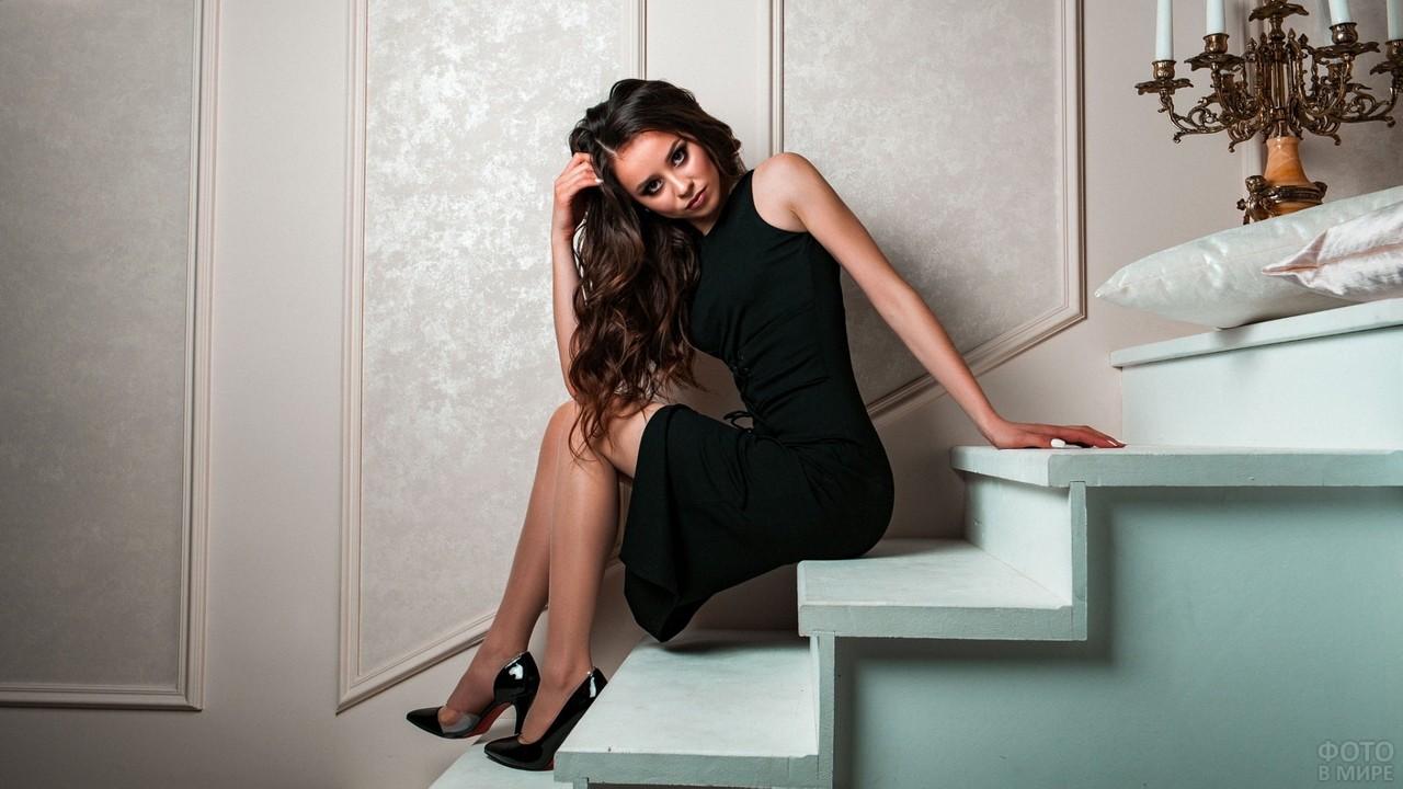 Девушка в чёрном платье на белой лестнице