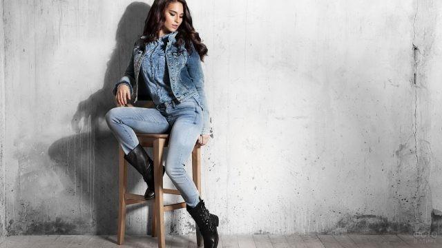 Девушка в джинсовой одежде на высоком табурете