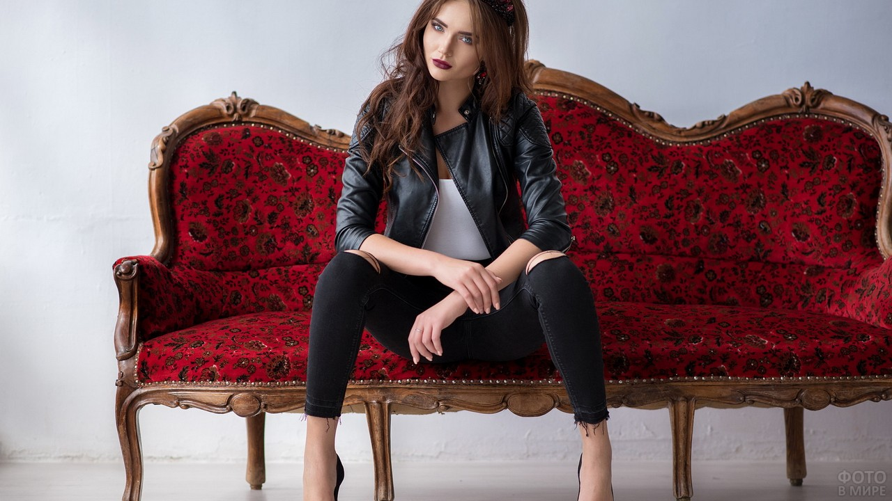 Девушка в кожаной куртке сидит на красной софе