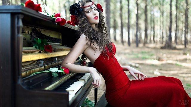 Девушка в красном платье облокотилась на пианино