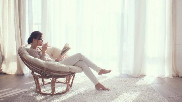 Девушка в кресле из ротанга пьёт чай за книгой