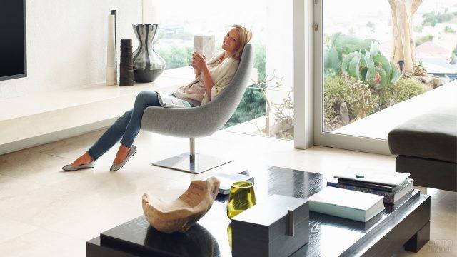 Девушка в кресле с бокалом в руках в светлой комнате