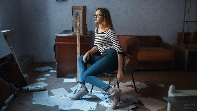 Девушка в очках в неубранной комнате