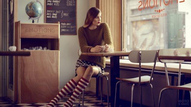 Девушка в полосатых гольфах в кафе
