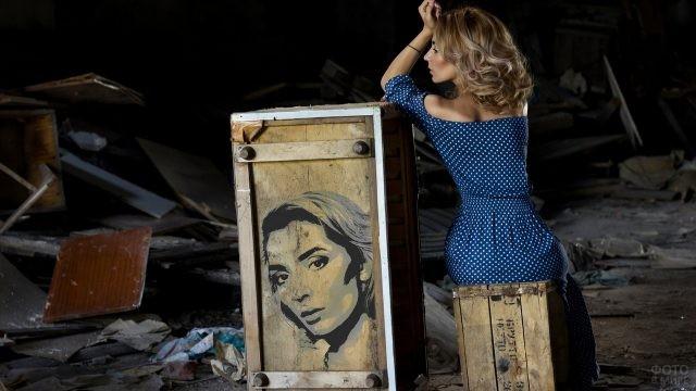 Девушка в синем платье сидит на ящиках