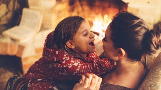 Мама с дочкой на диване у камина