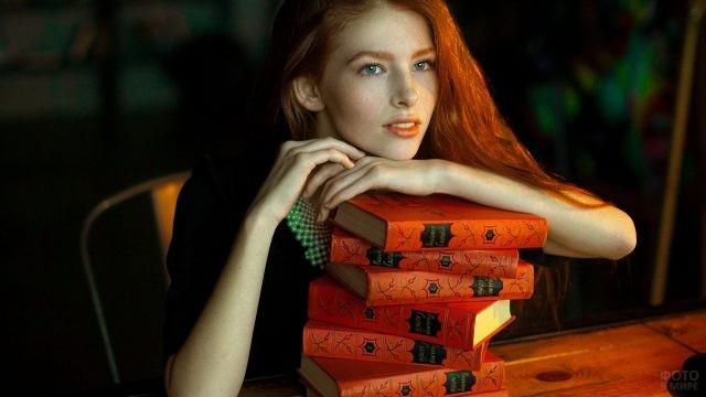 Рыжая девушка облокотилась на книги