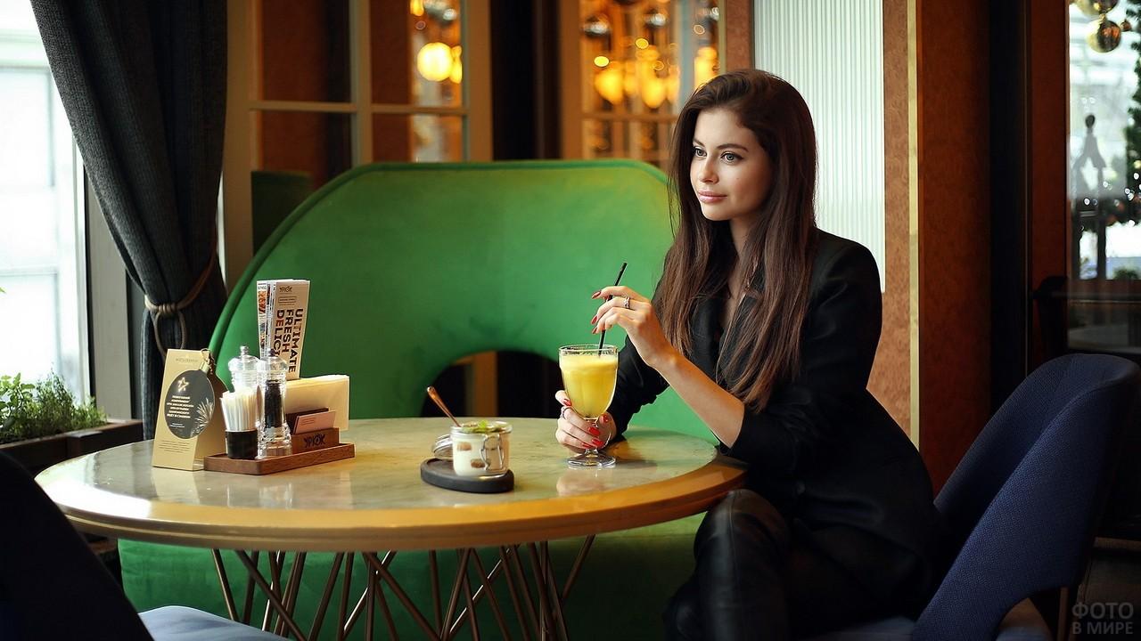 Шатенка в кафе пьёт сок