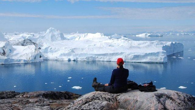 Девушка на горе смотрит на айсберг