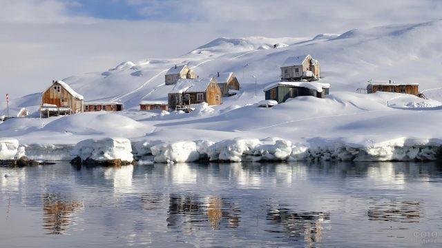 Домики в снегу возле океана