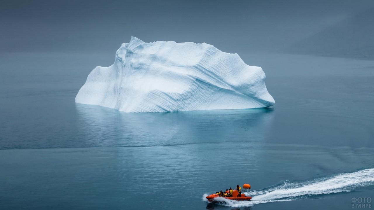 Оранжевый катер плывёт мимо айсберга