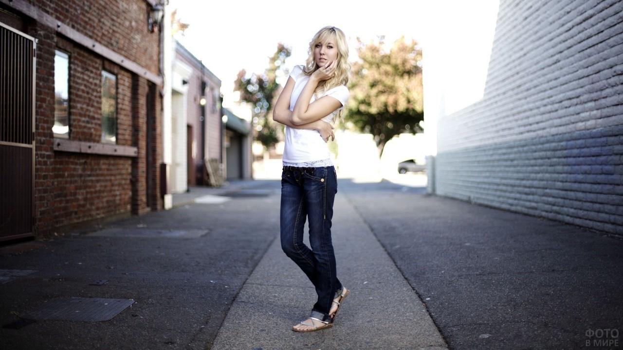 Блондинка в сланцах стоит в переулке