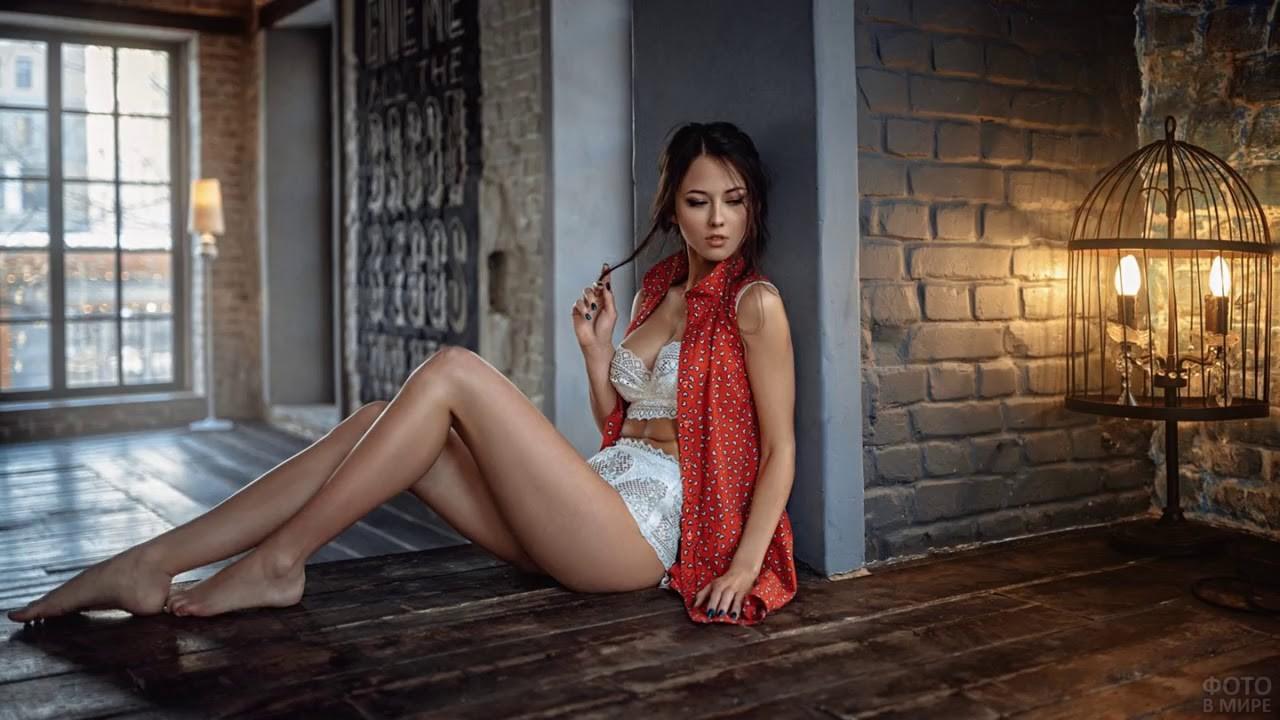 Босоногая девушка сидит на полу