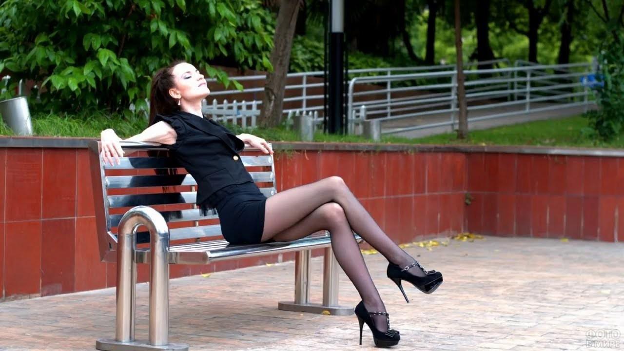 Брюнетка на шпильках облокотилась на спинку скамейки