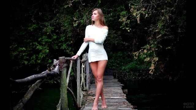 Девушка стоит босиком на мостике