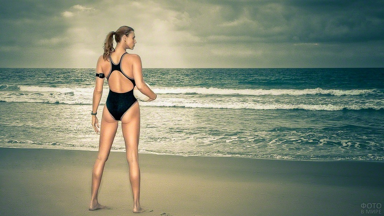 Самая высокая модель Ева Бэйбзилла стоит с мячом у моря