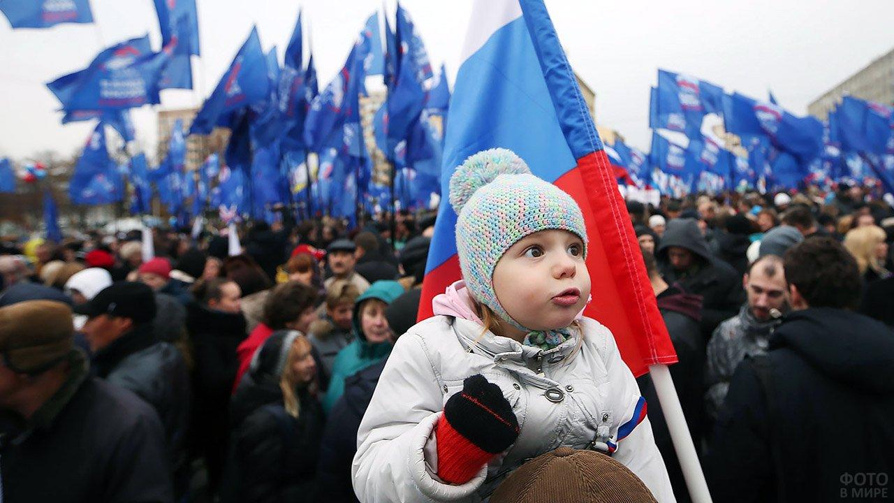 Малышка смотрит во все глаза на парад в День народного единства