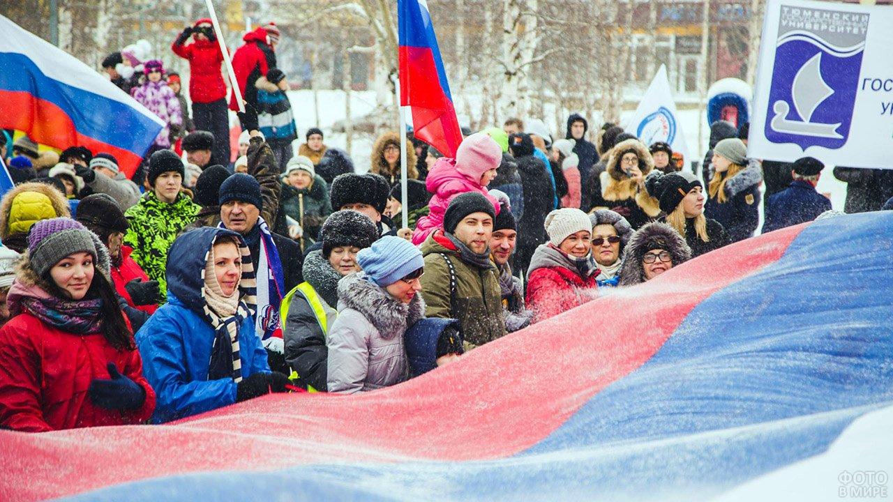 Жители Сургута держат огромный триколор на городском празднике