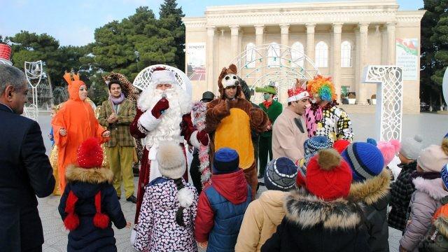 Дед Мороз и аниматоры в костюмах зверей развлекают детей в городском парке