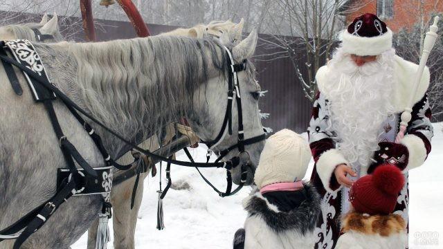 Дед Мороз и дети рядом с тройкой белых лошадей