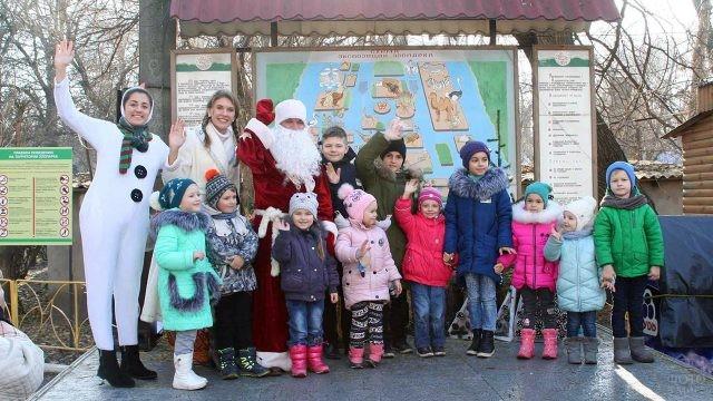 Дед Мороз и снеговик в компании малышей у стенда зоопарка