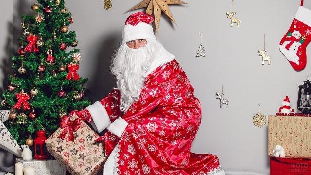 Дед Мороз кладёт подарок под ёлку