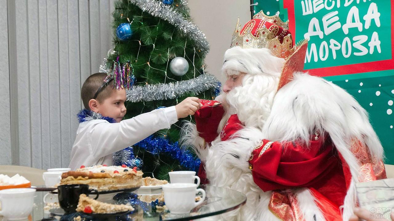 Дед Мороз пробует угощение из рук маленького мальчика