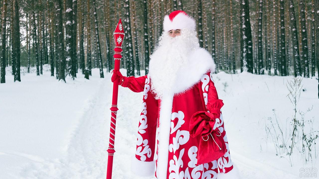Дед Мороз в красном кафтане с красным посохом в зимнем лесу
