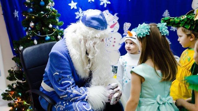 Дети в маскарадных костюмах и Дед Мороз разговаривают под ёлкой