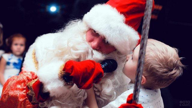 Мальчик рассказывает на ушко Деду Морозу стишок