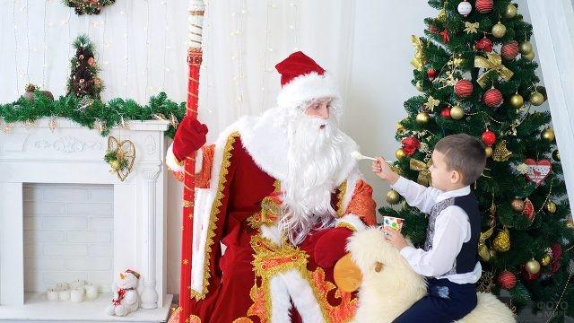 Малыш угощает Деда Мороза мороженым