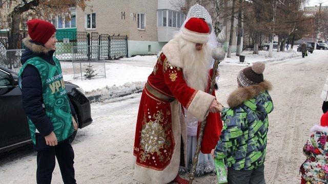 Нарядный Дед Мороз раздаёт подарки малышам на улице города