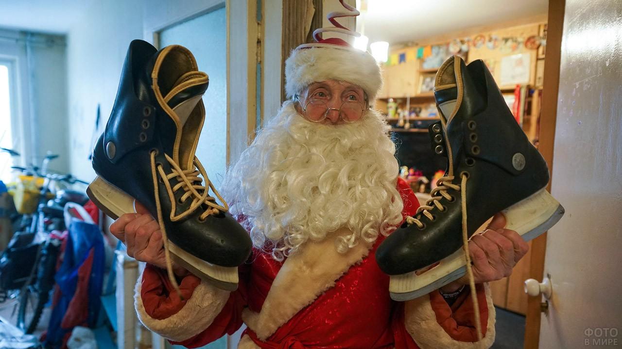 Старенький Дед Мороз с хоккейными коньками в руках