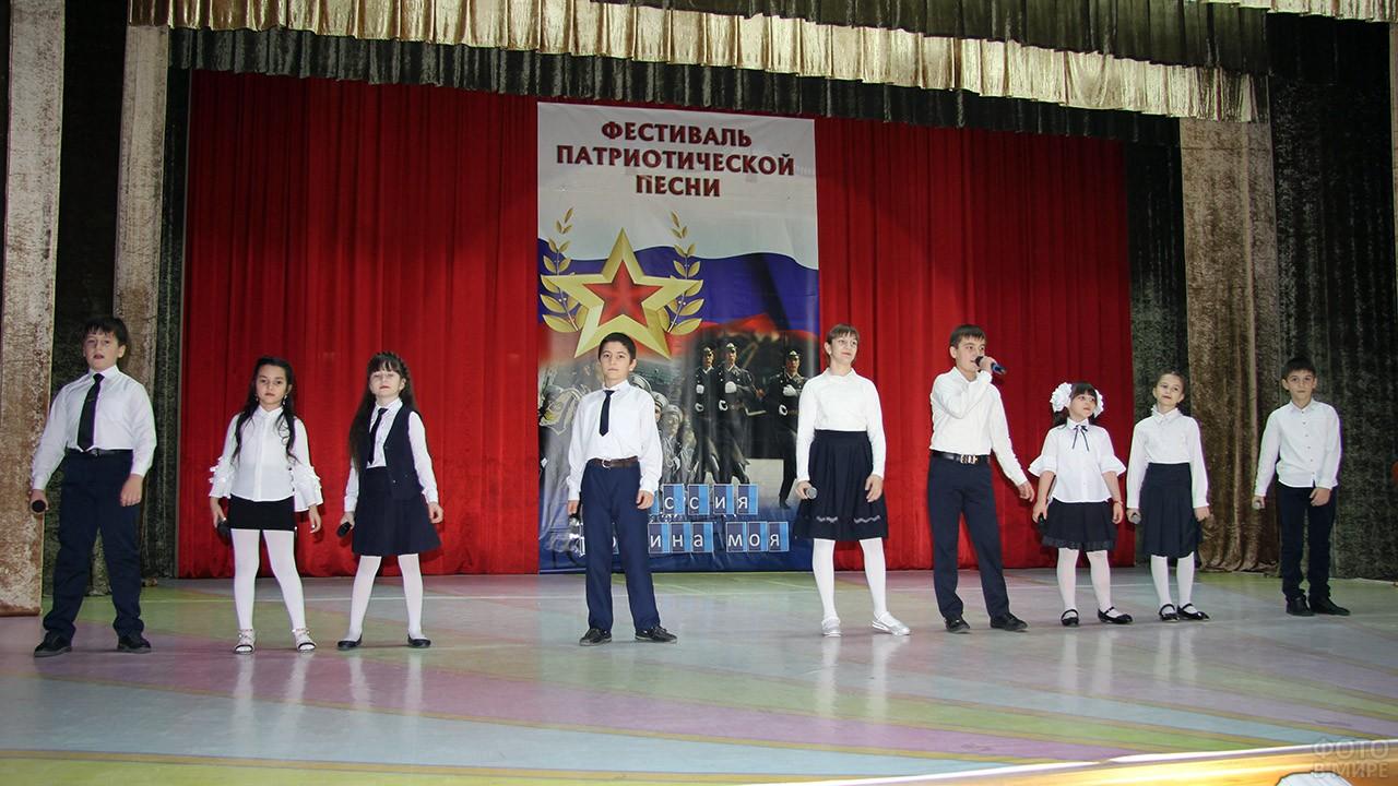 Дети на сцене исполняют патриотические песни